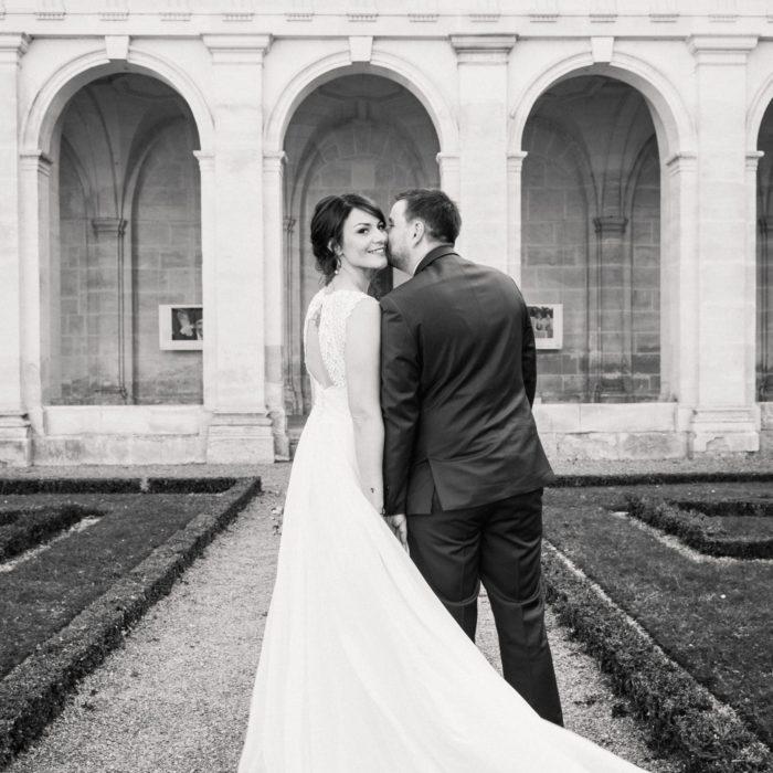 Photo d'un couple de mariés à la sortie de la cérémonie civile, photo prise par un photographe professionnel. Le marié embrasse la mariée sur la joue