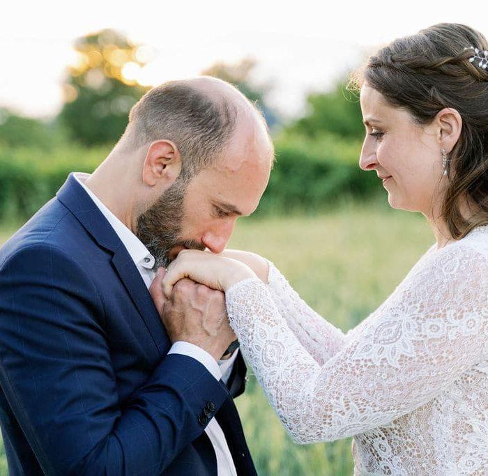 Photo d'un couple de mariés prise par un photographe de mariage. Le marié embrasse les mains de la mariée!