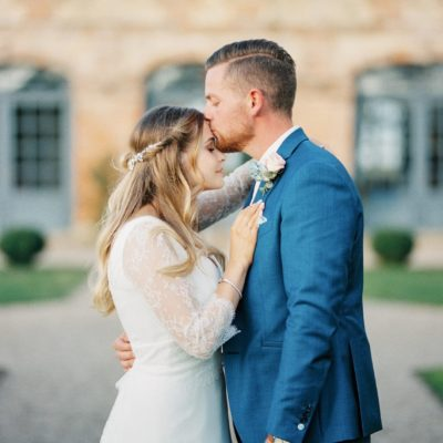 Photo d'un Photographe mariage d'un couple de mariés en tenues. Le marié embrasse le front de sa compagne