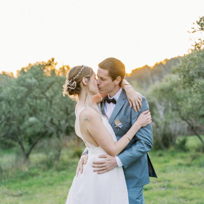 Photo d'un couple de mariés prisé par une photographe de mariage dans un champs d'oliviers, ils s'embrassent.