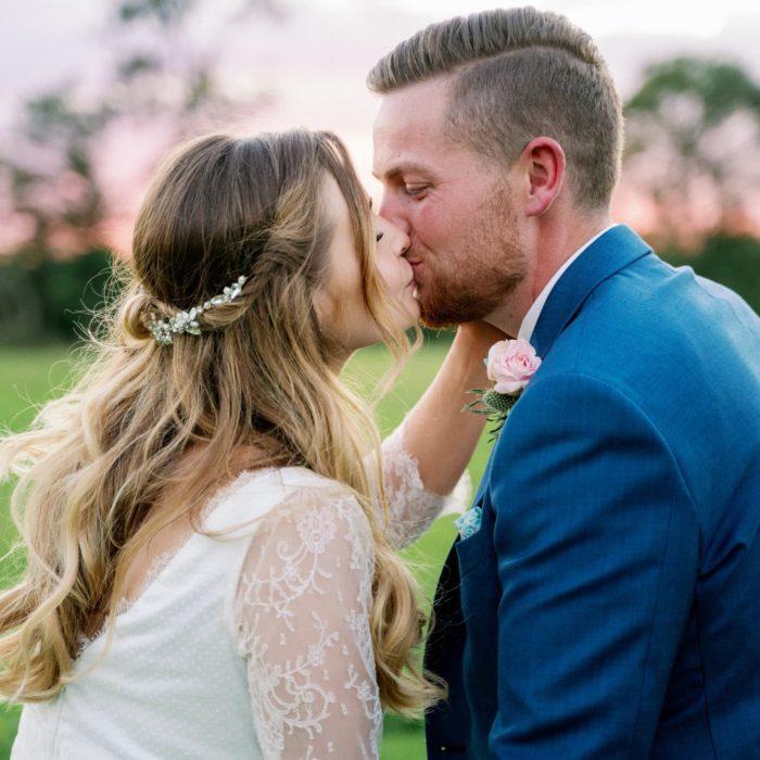Photo d'un photographe de mariage lors d'une séance couple, les mariés s'embrassent. Il y a un coucher de soleil derrière eux